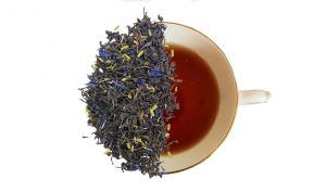 Lavender earl grey tea leaves over a brewed cup of tea