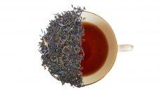 Earl grey tea leaves over top of a cup of earl grey tea