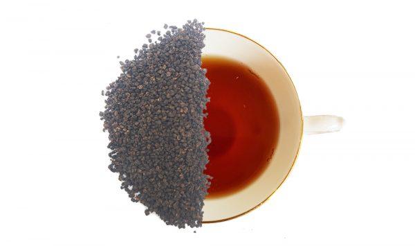 Irish breakfast loose leaf tea. Displays the loose leaf tea over half of a cup of brewed tea