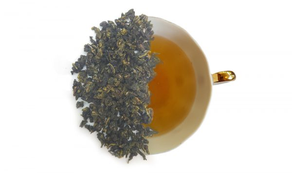 Sweet Milk Oolong tea leaves over a brewed up of tea. Product image