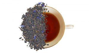 cream of earl grey loose leaf tea displayed over top of a cup of tea. split