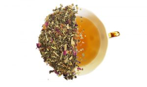 detox and cleanse tea blend tea leaves split over a brewed cup of tea