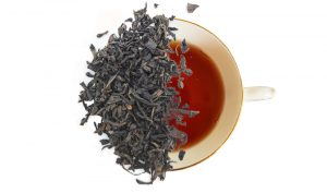lapsang souchong tea leaves displayed over a brewed cup of tea