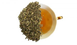 peppermint loose leaf tea leafs displayed overtop of a cup of tea
