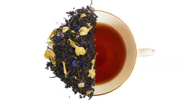 Jasmine black tea leaves displayed over a cup of brewed tea